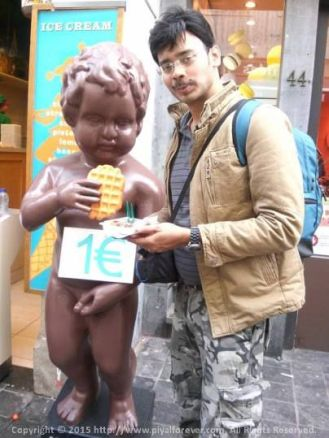Sharing a waffle with the legendary Manneken Piss at Brussels, Belgium